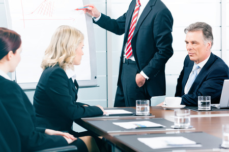 Business presentation within a team in office, a colleague is standing on the flip chart photo