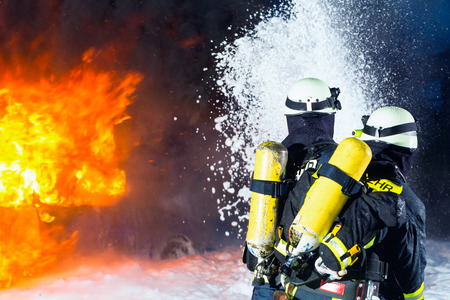 firefighter: Firefighter - Firemen extinguishing a large blaze, they are standing with protective wear in front of wall of fire Stock Photo