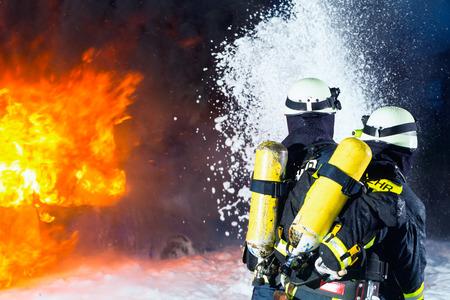 Firefighter - brandweer het blussen van een grote brand, staan ??ze met beschermende kleding in de voorkant van de muur van vuur Stockfoto - 26324824