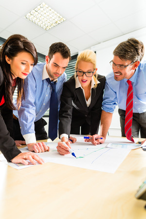 Four professionals in the office in business clothes when planning a strategy for the future of the business photo