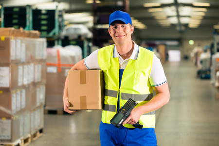 barcode scanner: Warehouseman with protective vest and scanner, scans bar-code of package, he standing at warehouse of freight forwarding company Stock Photo