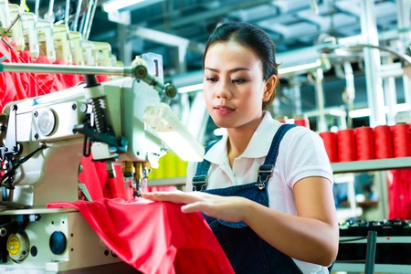 precisely: Seamstress or worker in factory sewing with industrial machine, she is very accurate