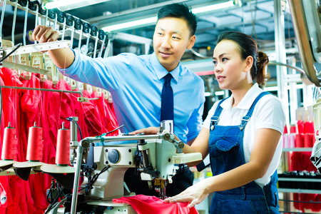Seamstress is new assigned to a machine in a textile factory, the foreman explains something photo