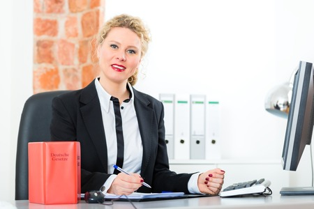 Young female lawyer working in her office with typical law book and writing document photo