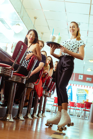 diner: Friends or couples eating fast food and drinking milk shakes on bar in American fast food diner, the waitress serving with roller-skates Stock Photo
