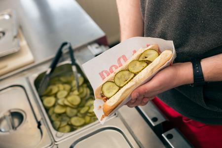 casse-cro�te: Hotdog - Salesman amical et ingr�dients frais dans un snack-bar de la restauration rapide Banque d'images