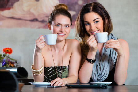 likeable: Young women or colleagues sitting in a cafe or restaurant, and flirting while working