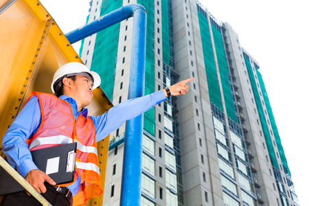 supervision: Chinese construction worker or supervisor or architect with clipboard on a building site in Asia