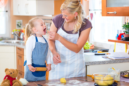 secure home: Family home baking - Mother and daughter baking cookies together at home Stock Photo