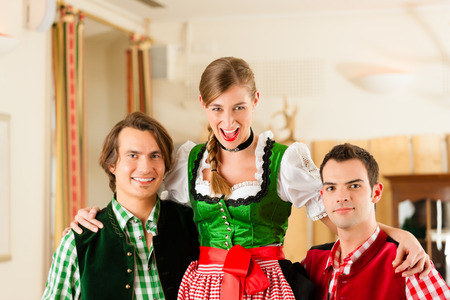 tracht: Young couple in traditional Bavarian Tracht in restaurant or pub, they might be the innkeepers with a guest Stock Photo