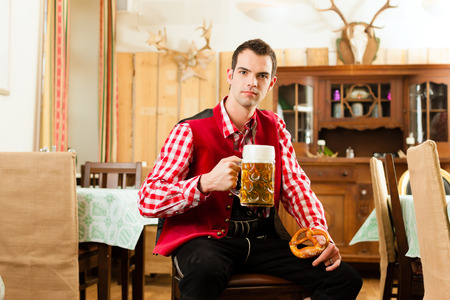 tracht: Young man in traditional Bavarian Tracht in restaurant or pub with beer and steins and pretzel Stock Photo