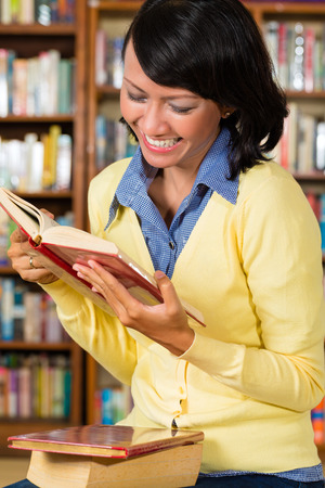 Student - a young Asian woman or girl learning in a library reading a book photo