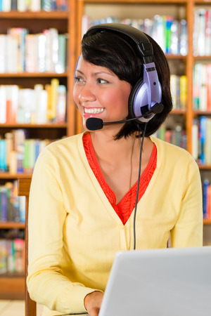 Student - Young woman in library with laptop and headphones learning and smiling photo