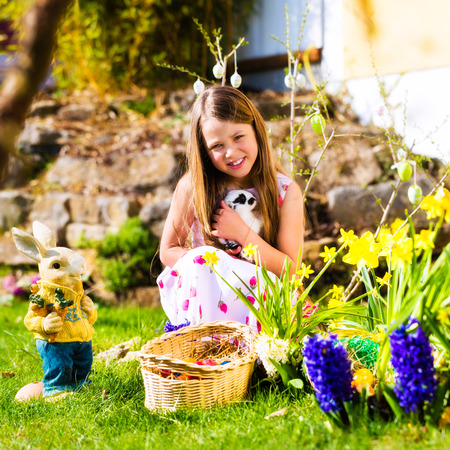 Little girl on an Easter Egg hunt on a meadow in spring, she holds a living bunny photo