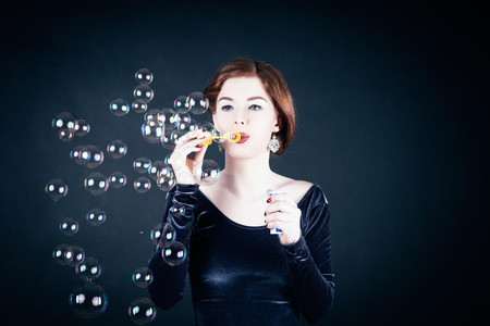 Girl making soap bubbles in front of dark background Stock Photo - 26361443