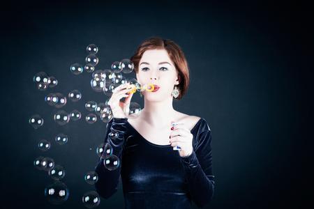 bursting: Girl making soap bubbles in front of dark background