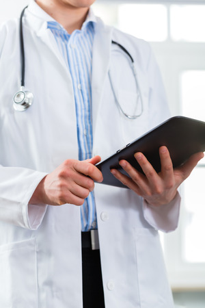 Young doctor standing in clinic reading a file or dossier on the tablet computer photo