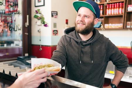 casse-cro�te: Hotdog - sympathique vendeur et le client dans un snack-bar de la restauration rapide