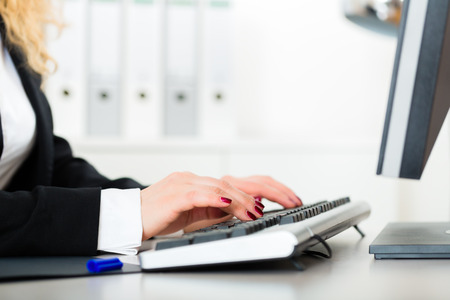 Young lawyer or business woman working in her Office, she works with computer and writing on the keyboard Stock Photo