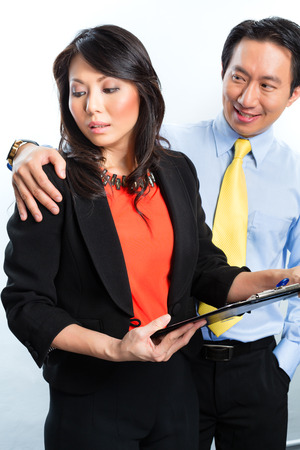 Asian Chinese Employee or secretary getting manager or business man sexual harassed or harassment and reject him photo