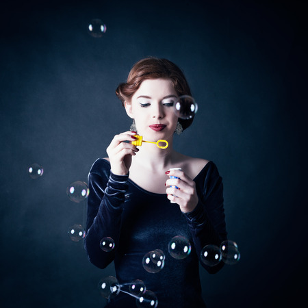 Girl making soap bubbles in front of dark background Stock Photo - 26361498