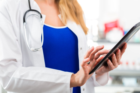Young female doctor standing in clinic reading a file or dossier on the tablet computer photo