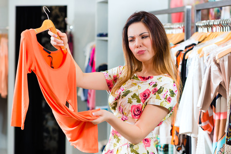 choosing clothes: Young woman having fun while fashion shopping in boutique or store