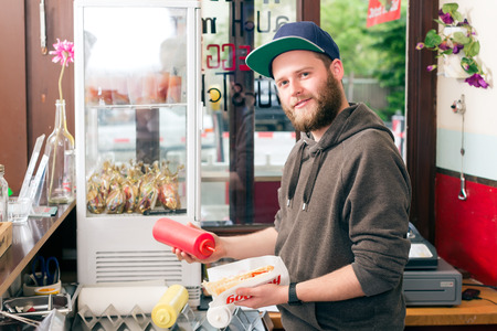 Hotdog - friendly salesman and fresh ingredients in a fast food snack bar Stock Photo