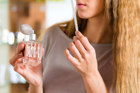 Young woman buying perfume in a shop or store, testing the fragrance with a paper tester Imagens