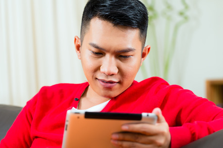 Young Indonesian man sitting with a tablet computer on a couch, maybe he writing, looking for emails or shopping online Stock Photo - 26449154