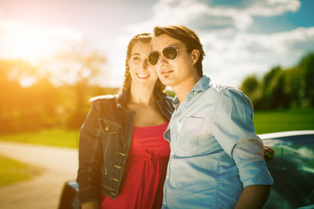 raod: Young hip couple - man and woman - with cabriolet convertible car in summer on raod trip Stock Photo