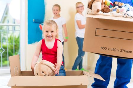 Maison de famille se déplaçant avec des boîtes pleines de choses, ils peignent les murs de leur nouvelle maison