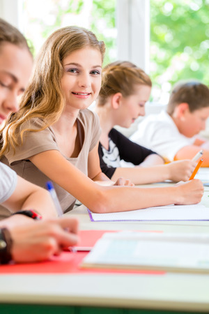 secondary schools: Students or pupils of school class writing an exam test in classroom concentrating on their work