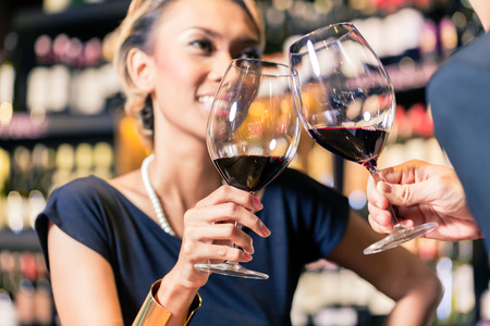 Close up of Asian couple clinking glasses in wine shop photo