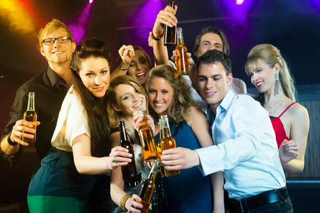 beer in bar: Young people in club or bar drinking beer out of a beer bottle and have fun