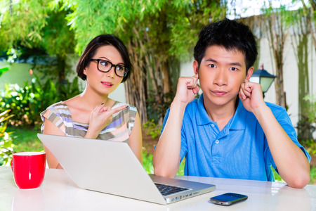 exasperated: Chinese mother talking to her son but will not listening, holding his ears with his hands refusing the good advice
