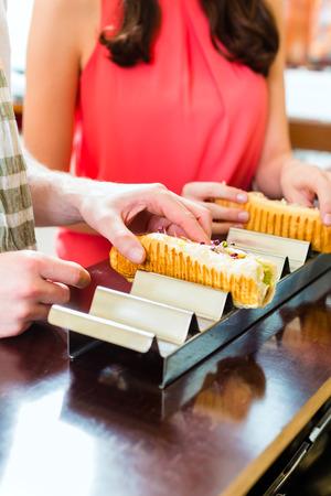 casse-cro�te: Hotdog - jeunes clients dans un snack-bar de manger de d�licieuses saucisses de restauration rapide