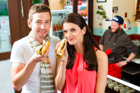 Hotdog - young customers in a snack bar eating delicious fast food sausages Stock Photo