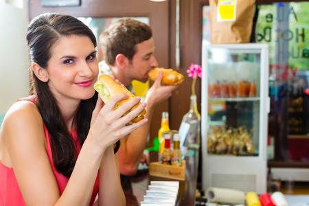 Hotdog - young customers in a snack bar eating delicious fast food sausages photo