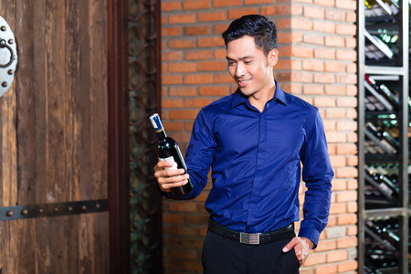 Asian man holding bottle of wine photo