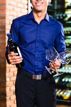 adult indonesia: Close up of man holding bottle of wine and two wine glasses Stock Photo