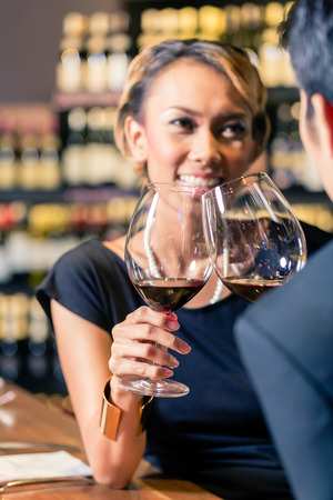 Close up of Asian couple toasting in wine shop photo