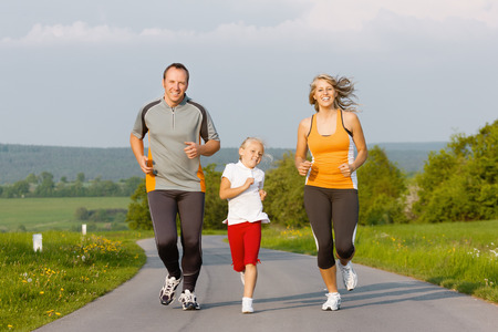 Family jogging for sport for fitness outdoors with the kids Stock Photo