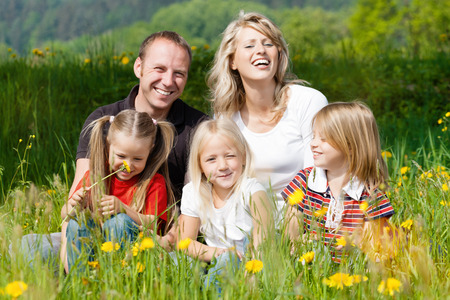 happy family with kids sitting in a meadow with dandelion in summer sun photo