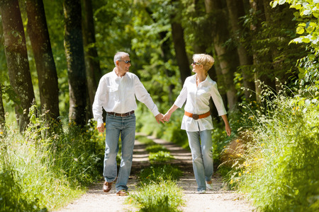 late summer: Mature or senior couple running, deeply in love having a walk holding each other tight in late spring or early summer Stock Photo