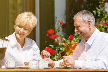 Senior couple of man and woman sitting in garden in front of home drinking coffee photo