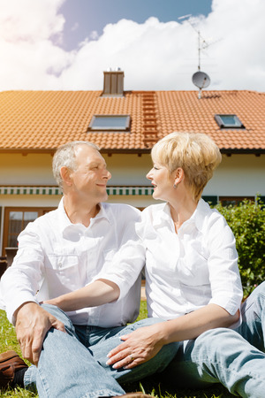 Senior couple of man and woman sitting in garden in front of home photo