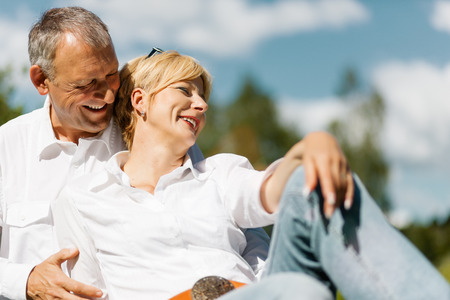 deeply: happy senior couple outdoors in spring arm in arm deeply in love