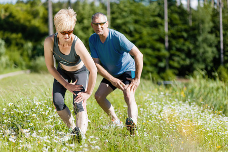 senior couple in jogging gear doing sport and physical exercise outdoors, stretching and gymnastics photo