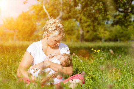 adult breastfeeding: Mother breastfeeding her baby on a great sunny day in a meadow